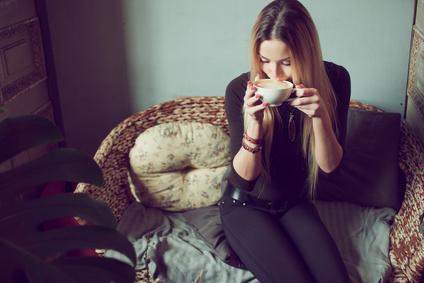 Frau mit Kaffee auf Rattansofa