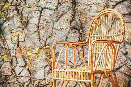 Naturrattan stuhl farbe honig vor einer bewacksenen gatenwand